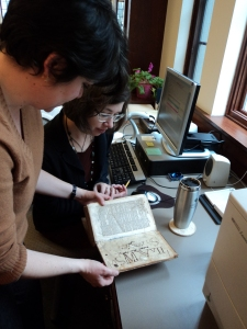 Elaine at work examining a volume with Sarah, a Wade Center volunteer.